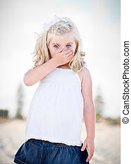 Adorable Blue Eyed Girl Covering Her Mouth Outside.