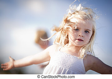Adorable Blue Eyed Girl Playing Outside with Her Family.