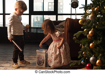 Adorable boy and girl decorating Christmas tree