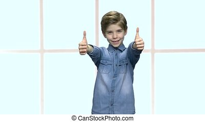 Adorable boy gesturing thumbs up with both hands. Cute...