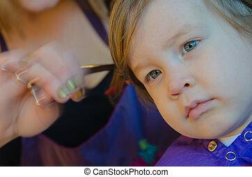 Adorable boy getting a hair cut