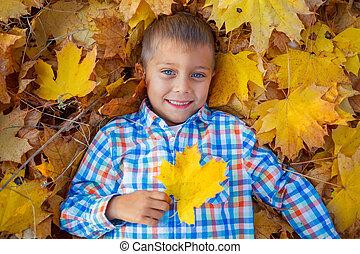 Adorable boy in autumn park