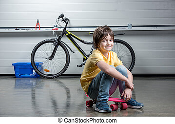 Adorable boy in sitting on penny board and looking at camera, bicycle behind