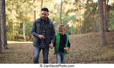 Adorable boy is walking in forest with his loving father holding his hand, bearded young man is talking, smiling and gesturing. Hiking, family and fatherhood concept.