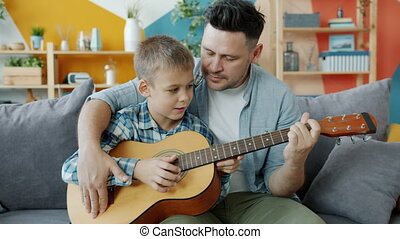 Adorable boy playing the guitar under guidance of caring ...