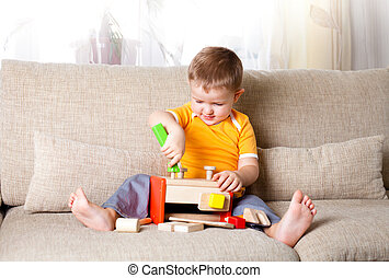 adorable boy playing with wooden building toys at home