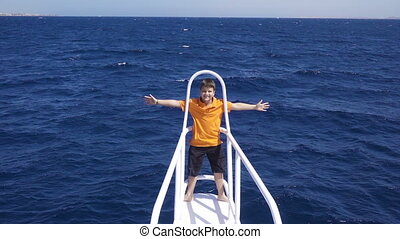 Adorable boy standing on the yacht bow on the wind, slow...