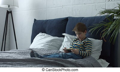 Adorable boy using smart phone playing on line