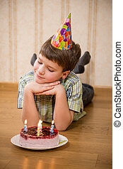 Adorable boy with birthday cake on the floor