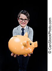 Adorable boy with piggy bank on black