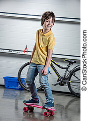 Adorable boy with pink penny board, bicycle behind