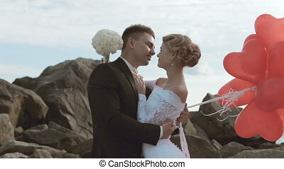 Adorable bride and groom stand with balloons in the form of heart in the rocks by the sea
