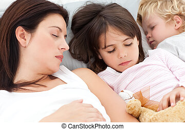 Adorable brother and sister sleeping with their mother in...