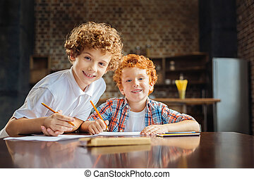 Adorable brother smiling into camera while drawing