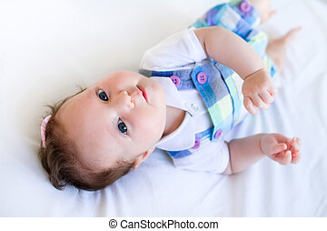 Adorable brunette baby girl in purple overalls