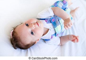 Adorable brunette baby girl in purple overalls