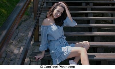 Adorable brunette woman sitting on stairs in outdoor