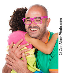 Adorable small caucasian child with curly hair wearing a pink blue and yellow dress. The girl and her father are playing with pink sunglasses.