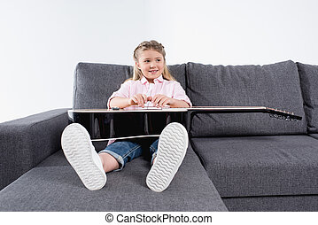 adorable caucasian girl practicing to play on guitar while sitting on sofa