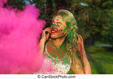 Adorable caucasian girl with curly hair posing in a cloud of pink dry paint, celebrating Holi festival
