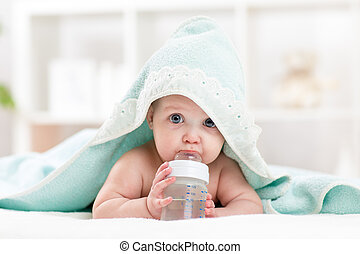 adorable child baby drinking water from bottle