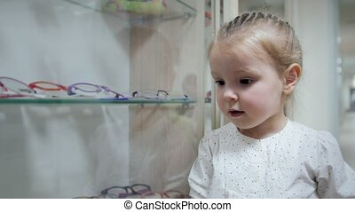 Adorable child blonde girl in ophthalmology clinic plays in...