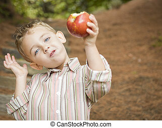 Adorable Child Boy Eating Red Apple Outside