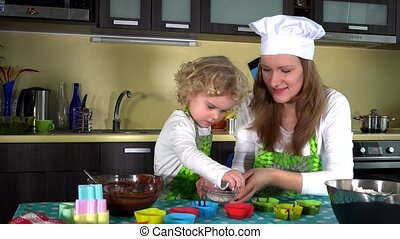 Adorable child decorating muffin cups. Little helper girl with mother