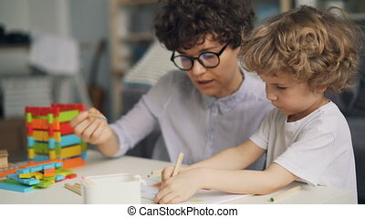 Adorable child drawing picture with pencils while mother...