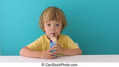 Adorable child drinking from box through straw - Cute...