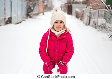 Adorable child girl playing outdoor with snow
