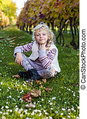 adorable child in daisy flowers and grass in autumn time