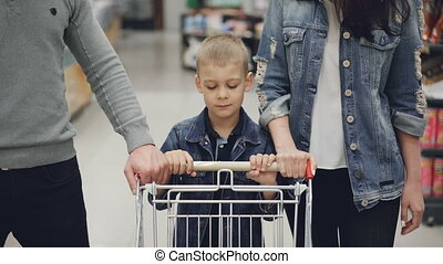 Adorable child is pushing shopping trolley inside food...