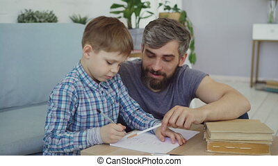 Adorable child junior school student is doing homework...