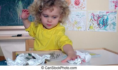 Adorable child kid doing mess on table in her room. Handheld...
