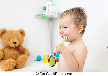 Adorable child learing how to brush his teeth in the ...