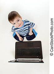 Adorable child playing with laptop. Top view.