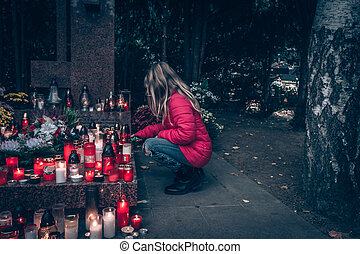 adorable child praying in the cemetery in autumn time