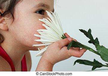 Adorable child smelling flower