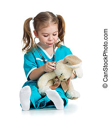 Adorable child with clothes of doctor examining hare toy over white