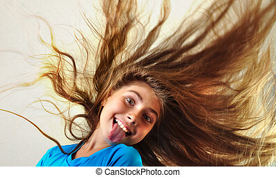 adorable child with long floating hair sticking her tongue out