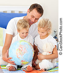 Adorable children and their father looking at a terrestrial globe sitting on bed