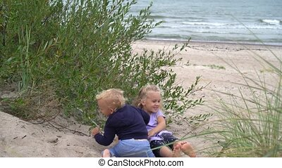 Adorable children fighting on dune sand. Brother and sister ...