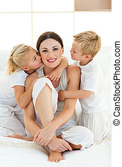 Adorable children kissing their mother sitting on a bed