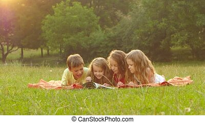 Adorable children reading a book on a lawn together summer...