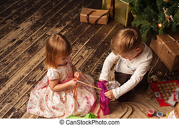 Adorable children sitting next to Christmas tree