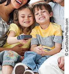 Adorable children watching TV with their parents