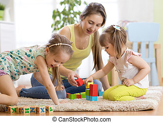 Adorable children with mom playing colorful toys