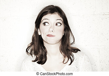 Portrait of a beautiful young woman with her eyes wide open, glancing sideways, she's looking completely clueless in the cutest manner possible.