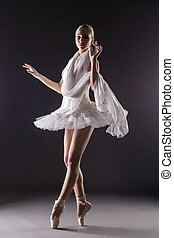 Adorable contemporary ballerina dancing in studio